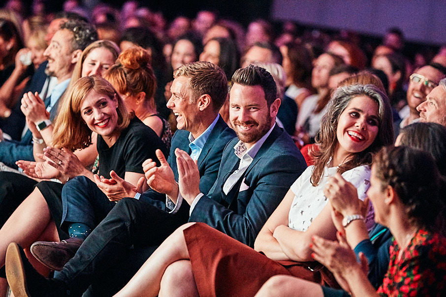 people in audience at conference laughing and clapping
