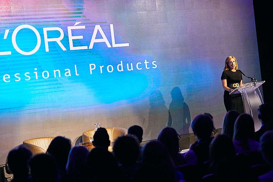 woman presenting to audience onstage, at L'Oreal conference