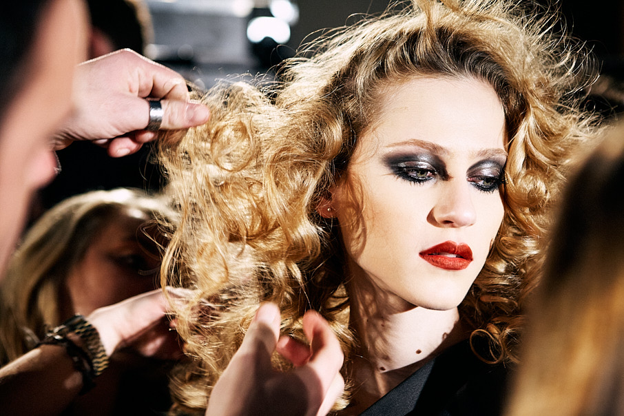 model having hair finished backstage at fashion show