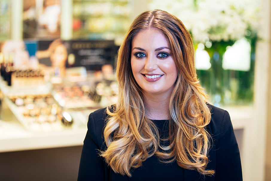 headshot of woman in fragrance store smiling at camera