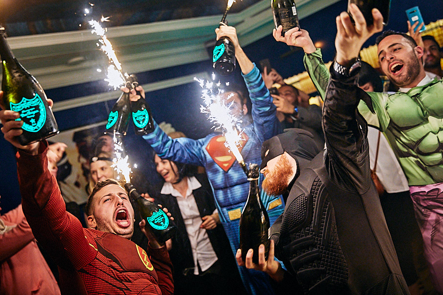 waiters dressed as superheroes holding up bottles of champagne and sparklers at party