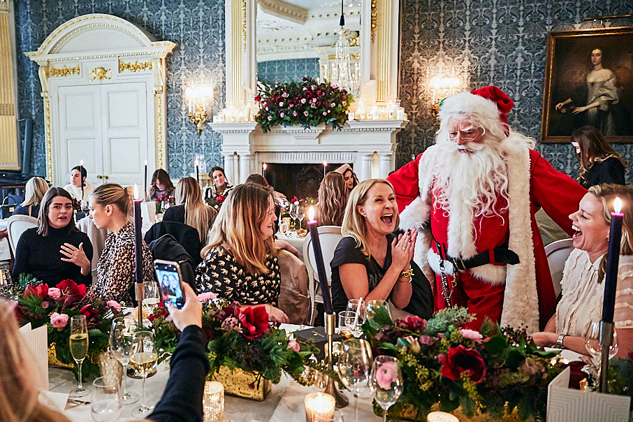 Father Christmas talking to laughing women at PR Christmas lunch