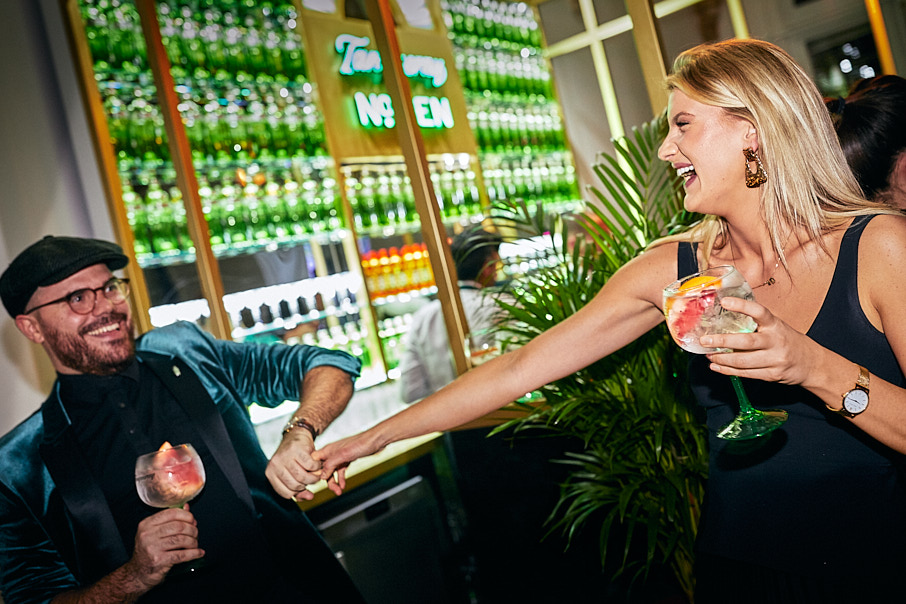 Cool man and stylish woman dancing with drinks at Tanqueray bar